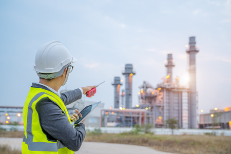 young engineer working at power plant with computer tablet and walky-talky radio communication.