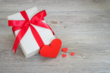 white gift box red ribbon and red heart on the vintage wooden table.