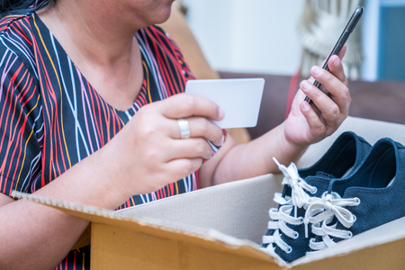 young asian woman received online shopping parcel opening boxes and buying fashion items with credit card Standard-Bild
