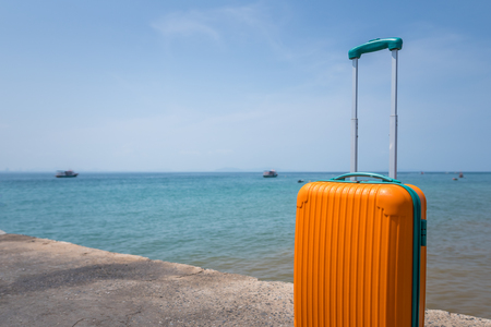Big orange suitcase on the ocean beach and blue sky background. Vacation concept.