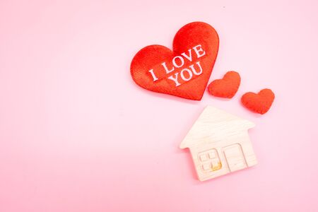 Text I LOVE YOU on the red heart with small house on the pink background, Family love concept.