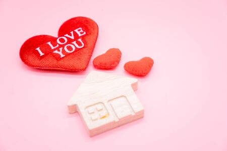 Text I LOVE YOU on the red heart and small wooden house on pink background, Family and love concept.