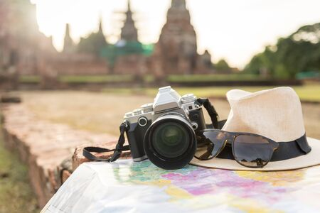 Retro camera on map with hat, sunglass on Ayutthaya Historical National Park Background. Standard-Bild