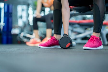 Body and mind workout in fitness gym studio, Sports woman taking dumbbell from the floor.