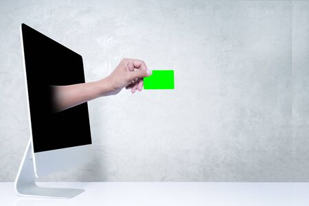 Hand giving credit card out of personal computer screen. Online shopping concept. Standard-Bild