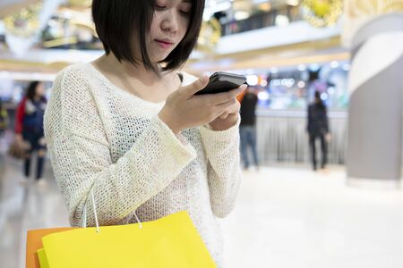 Young Asian female with shopping bag and use smartphone standing in the shopping mall