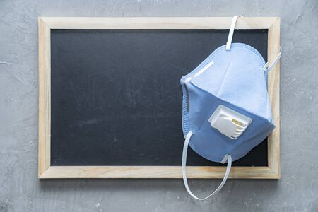 Empty chalkboard with medical mask hanging on the wall for insert text