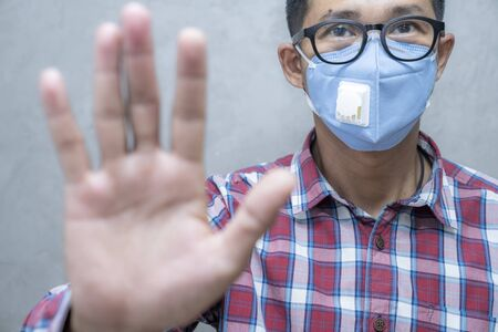Asian man wear medical mask standing show palm hand to stop the virus