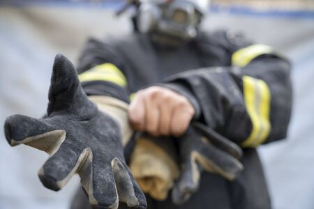 Firefighter wearing glove and safety suite ready to rescue, fire safety concept Standard-Bild