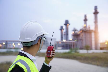 rear of engineer working with radio communication at power plant