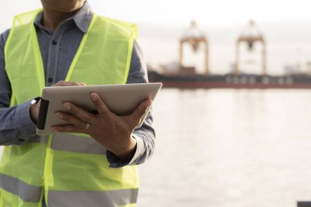 Logistic engineer using digital tablet working at cargo shipping port Standard-Bild