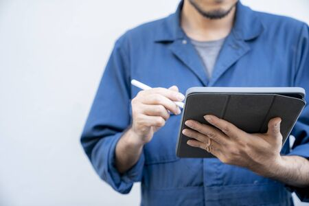 Technician wearing uniform working with digital tablet on white background