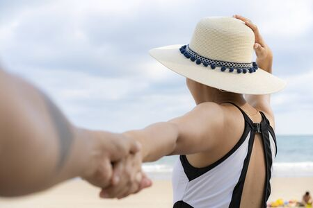 Rear of female in swimming suit and weave hat and holding hands friend standing on the beach, Vacation and summer travel concept