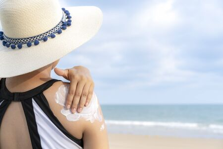 Rear of female in swimming suit and wear weave hat applying sunscreen with sea beach background