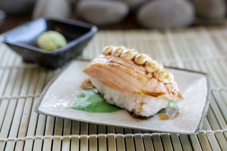 One sushi salmon with mayonnaise sauce topping on the Japanese traditional dish