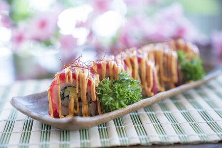 Tuna sushi roll with chili topping on dish, Japanese food