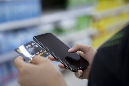 Hands holding smartphone and credit card for pay order online Standard-Bild