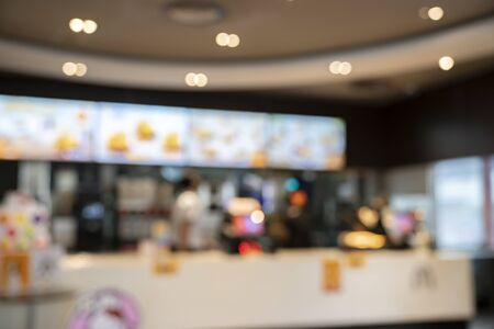 Blur counter restaurant shop or cafe restaurant with abstract bokeh light image background.