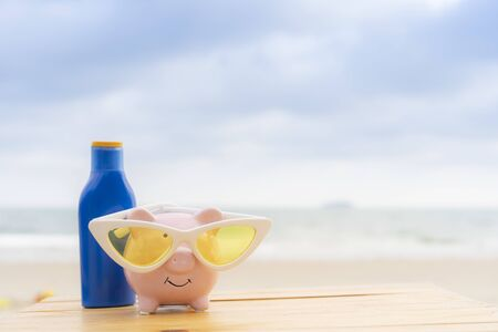 Pink piggy bank with sunblock bottle on the wooden table with ocean background, Money saving for vacation and travel concept Standard-Bild