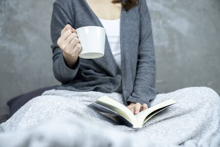 Part of girl holding coffee cup and reading a book on the bed, concepts of home and comfort.