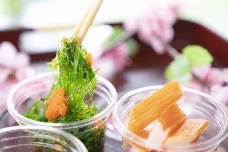 Close-Up of hands with chopstick take a seaweed salad from food delivery package Standard-Bild