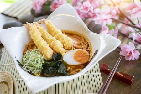 Hot and spicy soup ramen with shrimp tempura and boiled eggs in the japan bowl