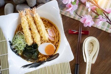 Top view of hot and spicy soup ramen with shrimp tempura and boiled eggs in the japan bowl Standard-Bild
