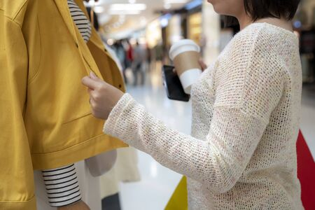 Part of female buying fashion clothes at shopping mall