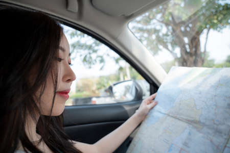 Traveler girl sitting in the car looking map, Journey travel concept 免版税图像