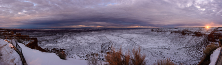Magnificent sunset on the top of canyon (top of the Moki Dugway). Infinity prairie extend to the horizon fully covered with fresh snow and tiny road is disappear in it.