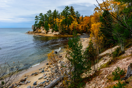 Stone coast in Pictured Rocks National Lakeshore, Munising, MI, USA. Autumn forest on the background