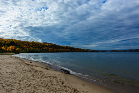 Sand coast in Pictured Rocks National Lakeshore, Munising, MI, USA. Logs on the foreground. Autumn forest on the background.