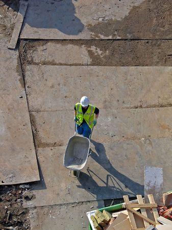 aereal: Single person using a wheelbarrow on a buildingplace