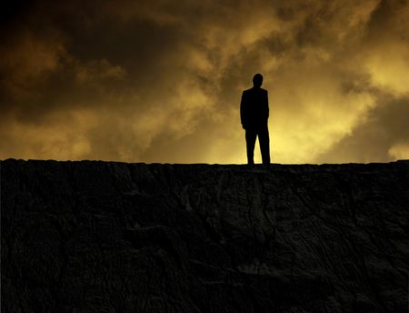 Man standing on a mountain at sundown, looking at bottomless hole