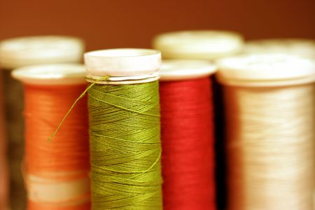 Spools of sewing thread in green, orange and red