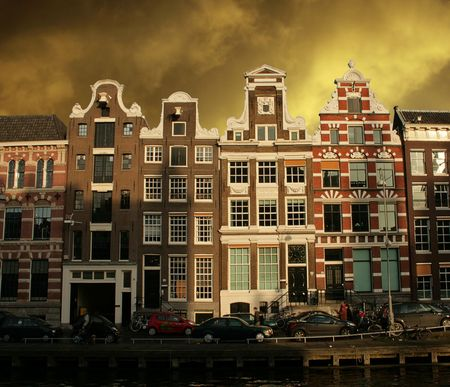Monumental Dutch houses in Amsterdam with cars, people, canal and dramatic sky Stock Photo