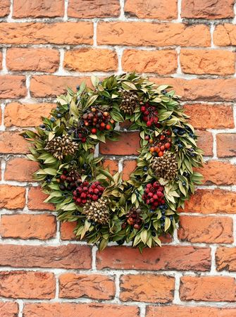 Garland or wreath with dried leaves and berries in front of a red brick wall photo