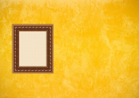 Empty baroque picture frame with copyspace on a yellow or gold grunge stucco wall Stock Photo
