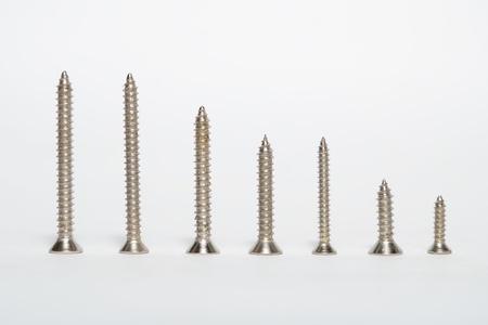 Tornillos de metal sobre un fondo blanco Foto de archivo