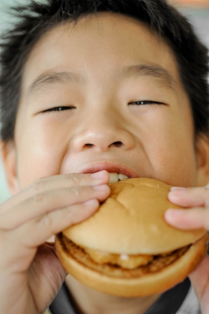 Little asian boy eating a hamburger