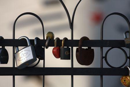 paling: Many key locks on a fence. White ship as a background Stock Photo