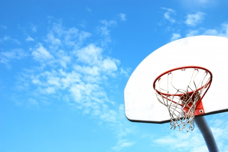Outdoor basketball hoop with blue sky and clouds