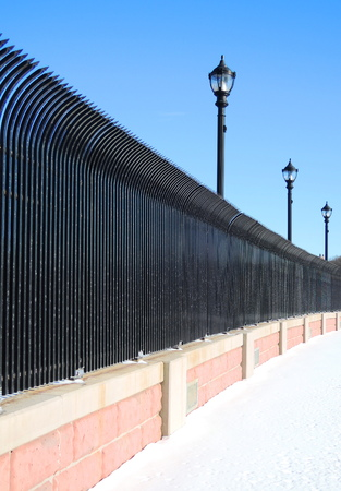 Street and a black steel fence in winter