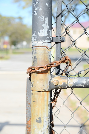 locked up in a cage: Chain on the fence Stock Photo