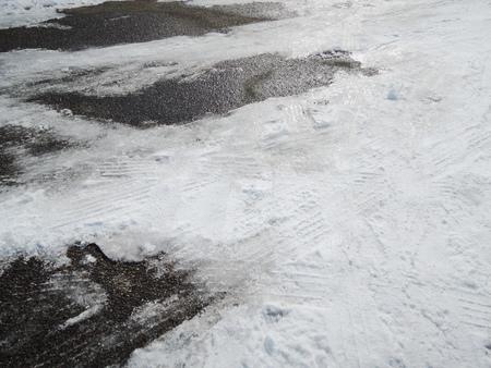 Sporen van autobanden in dunne laag eerste sneeuw