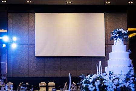Vorderansicht des Hochzeitsraumes mit leerem weißem Projektorschirm Standard-Bild