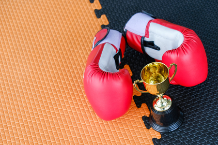 Golden trophy cup with red boxing gloves on black and orange background Stock Photo