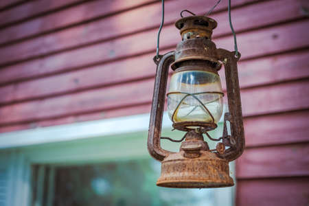 vintage rusty kerosene lamp hanging on the background of the wall. outdoors