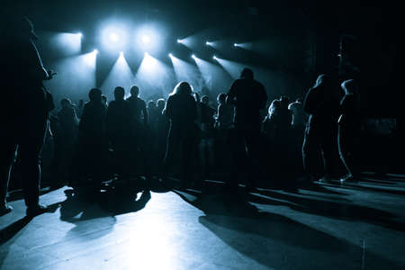 A group of people waiting for a concert in a small club on the background of a stage with rays of light in the dark