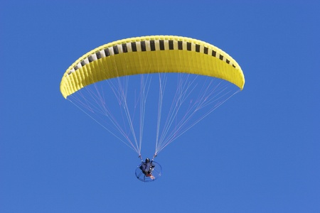 Yellow Parachute with motorized chair with blue sky background